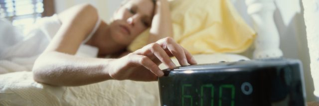 woman lying in bed and reaching for her alarm clock