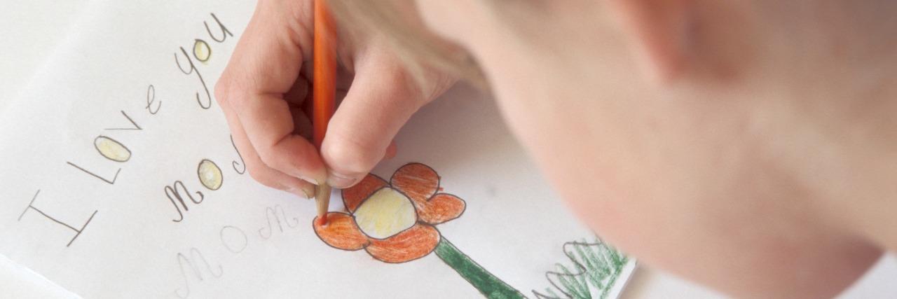 Girl making card for mom.