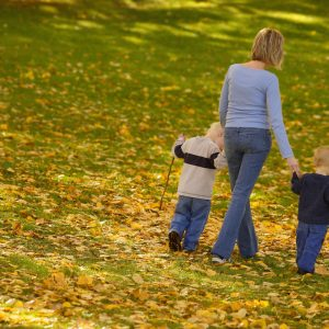 Mother walking on grass, holding hands of her two sons