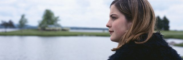 Woman sitting near lake, looking at landscape