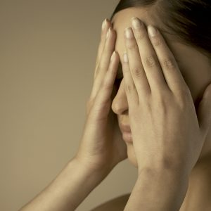 woman covering eyes with hands