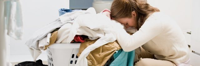 woman feeling overwhelmed leaning on basket of laundry