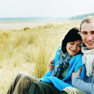 A couple, sitting on a beach