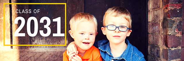 Twin boys with blonde hair. One wears glasses and the other has Down syndrome.