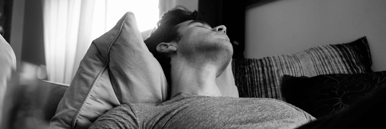 black and white photo of man laying in bed