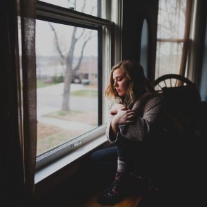 woman sitting beside window in darkened room looking out with sadness