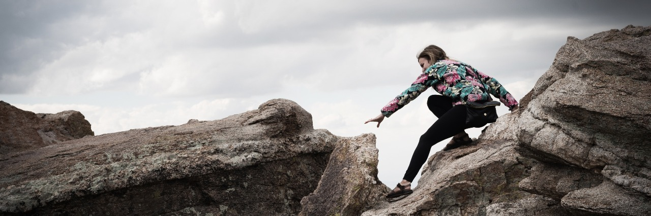 woman atop a rock with stormy clouds overhead as she reaches for the next one