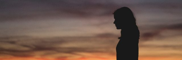 woman silhouetted against sunset sky