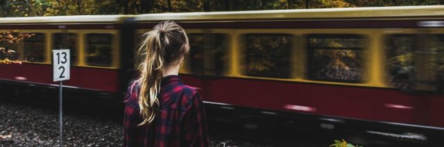 young woman watching train pass by in wooded area