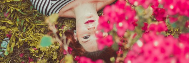 young woman lying among pink flowers in spring garden