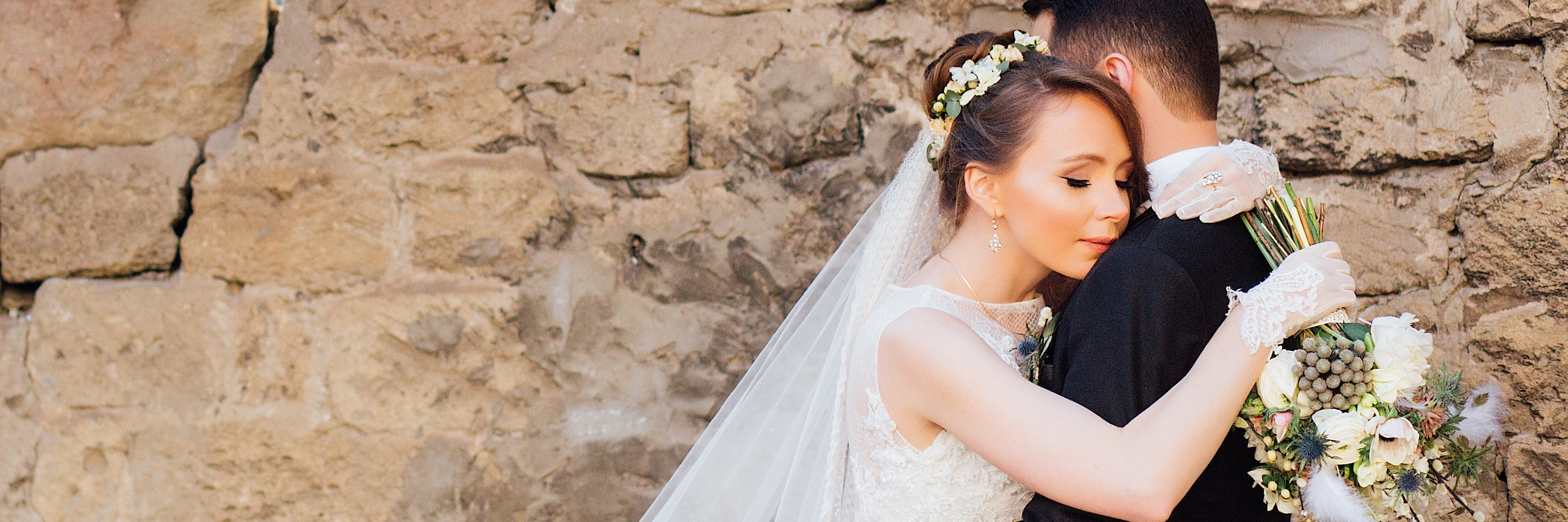newly wed husband and wife embracing before stone wall