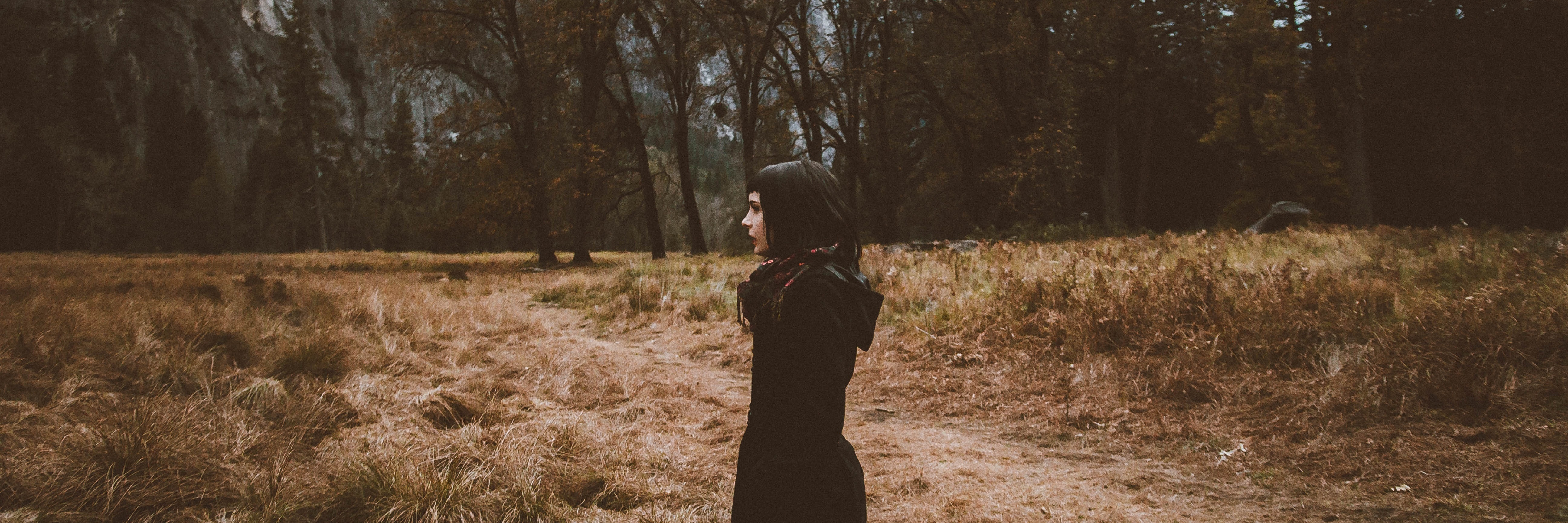 young woman in profile wearing dark clothes in nature by trees