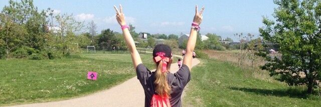 girl walking down a path with her hands raised in peace signs
