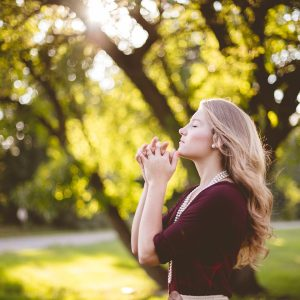 blonde woman in nature in front of tree praying