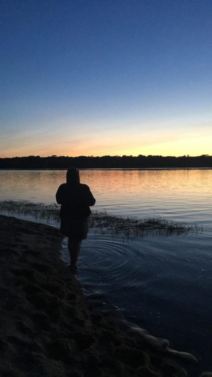 woman standing at the edge of a lake looking at the sunset