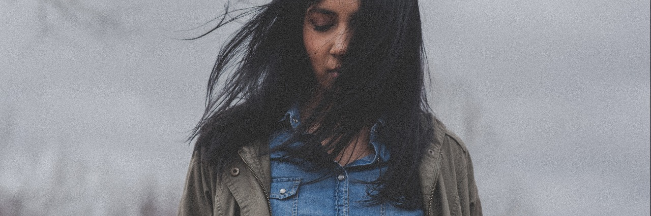 image of dark haired woman standing in front of cloudy sky with hair partly covering face