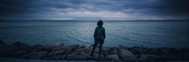 woman standing in front of stormy sea and stormy sky