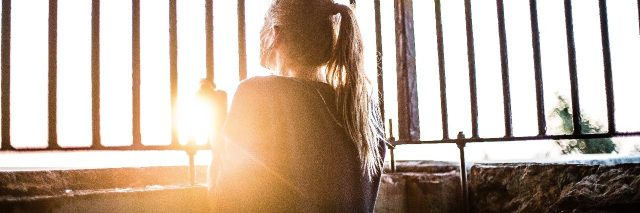 young woman standing in sunlight surrounded by bars