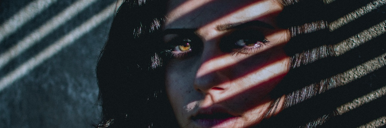 woman with shadows from blinds