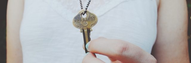 photo of woman holding key with word fearless printed onto it