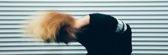 woman with blonde hair shaking her hair