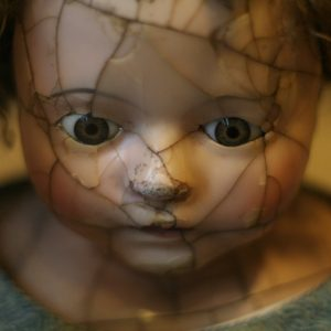 Close up of a doll's face with a shattered face