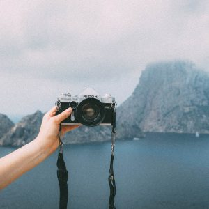 person holding camera out for selfie on island