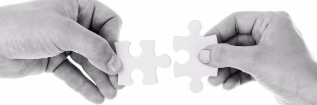 black and white image of hands holding jigsaw pieces