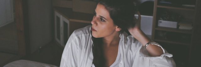 woman with dark hair sitting on bed looking away from camera