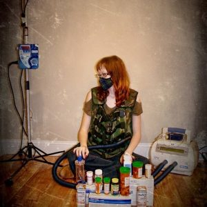 woman sitting on the floor with a mask over her mouth and pill bottles in front of her