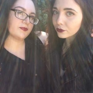 two female friends wearing black clothes and purple lipstick and smiling