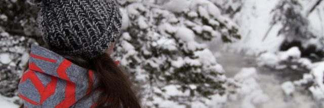 woman in snowy woods with long hair and hat