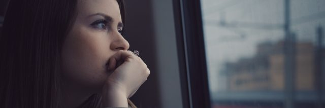 young woman staring out of public transport window looking pensive or anxious