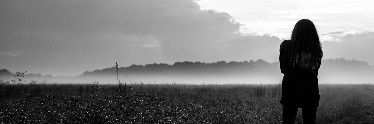 black and white woman standing in front of misty field