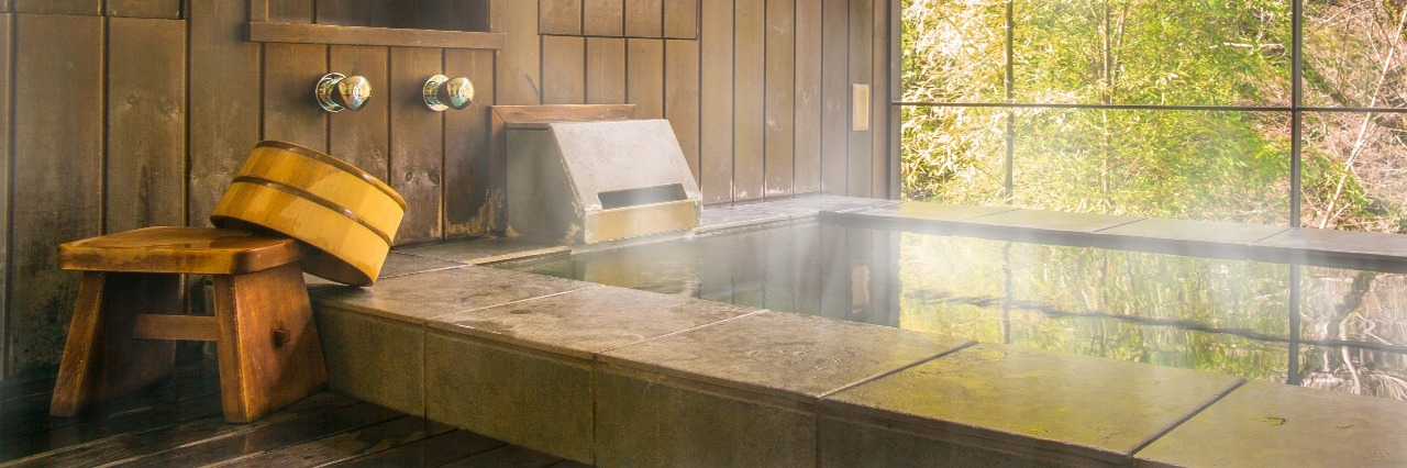 close up of japanese onsen or hot thermal bath filled with golden light