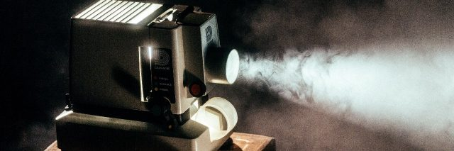 old movie projector sitting on wooden table with light shining through fog