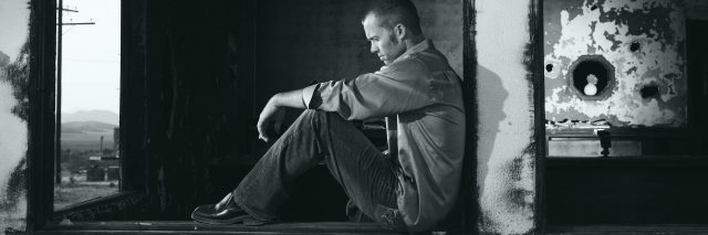 man sitting in derelict building looking depressed