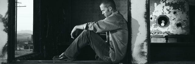 man sitting in derelict building looking depressed