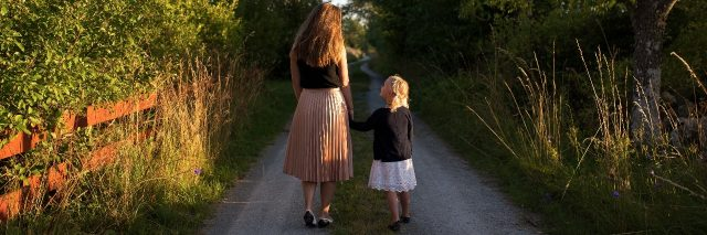 mother and daughter walking hand in hand down beautiful country lane while daughter looks up at mother