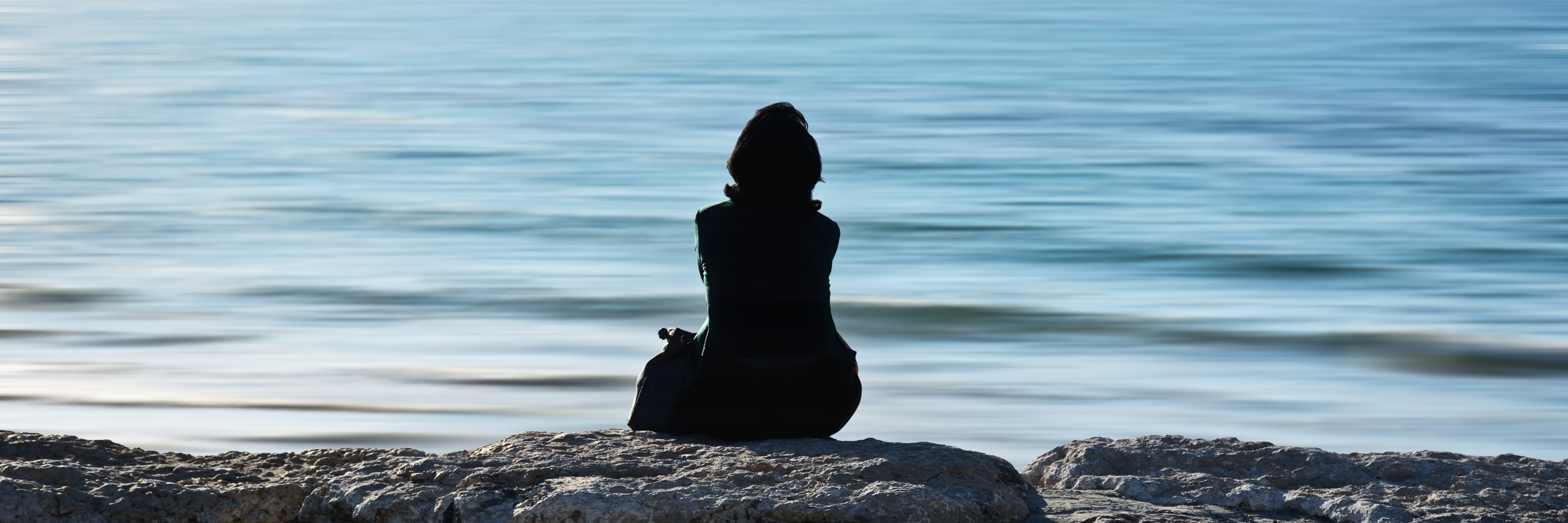 woman sitting alone in front of ocean with seagull in distance