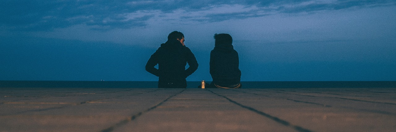 two people sitting on edge of pier or platform with dark clouds in distance and drink can between them