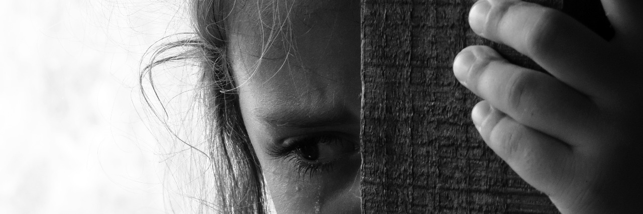 teenage girl behind wooden beam with tears in her eyes