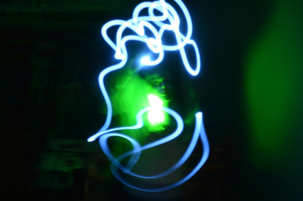 person with green light and blue light painting blur