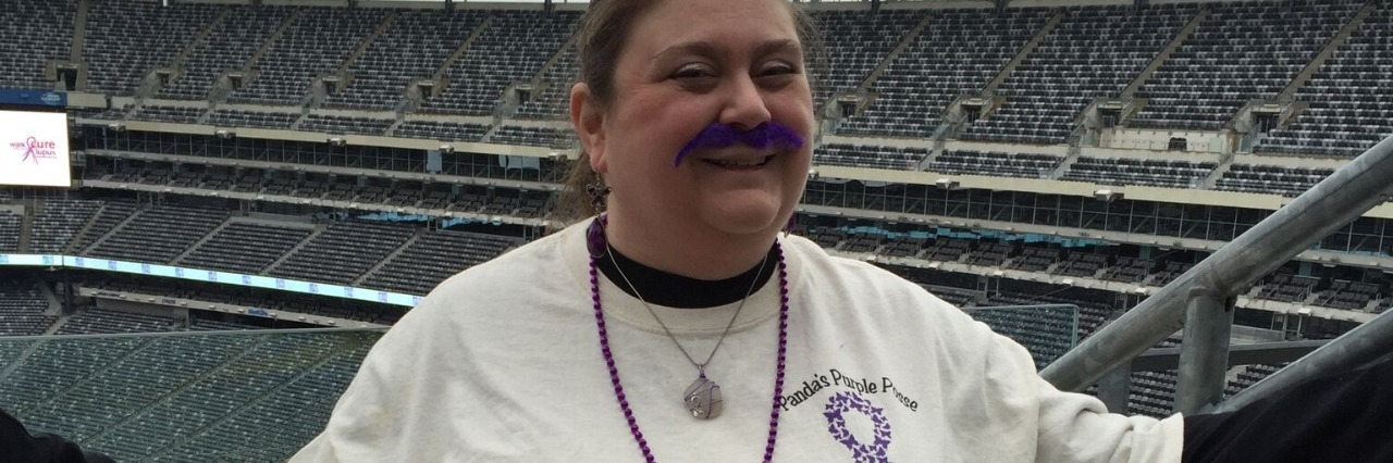 woman wearing a lupus awareness tshirt and standing in a football stadium