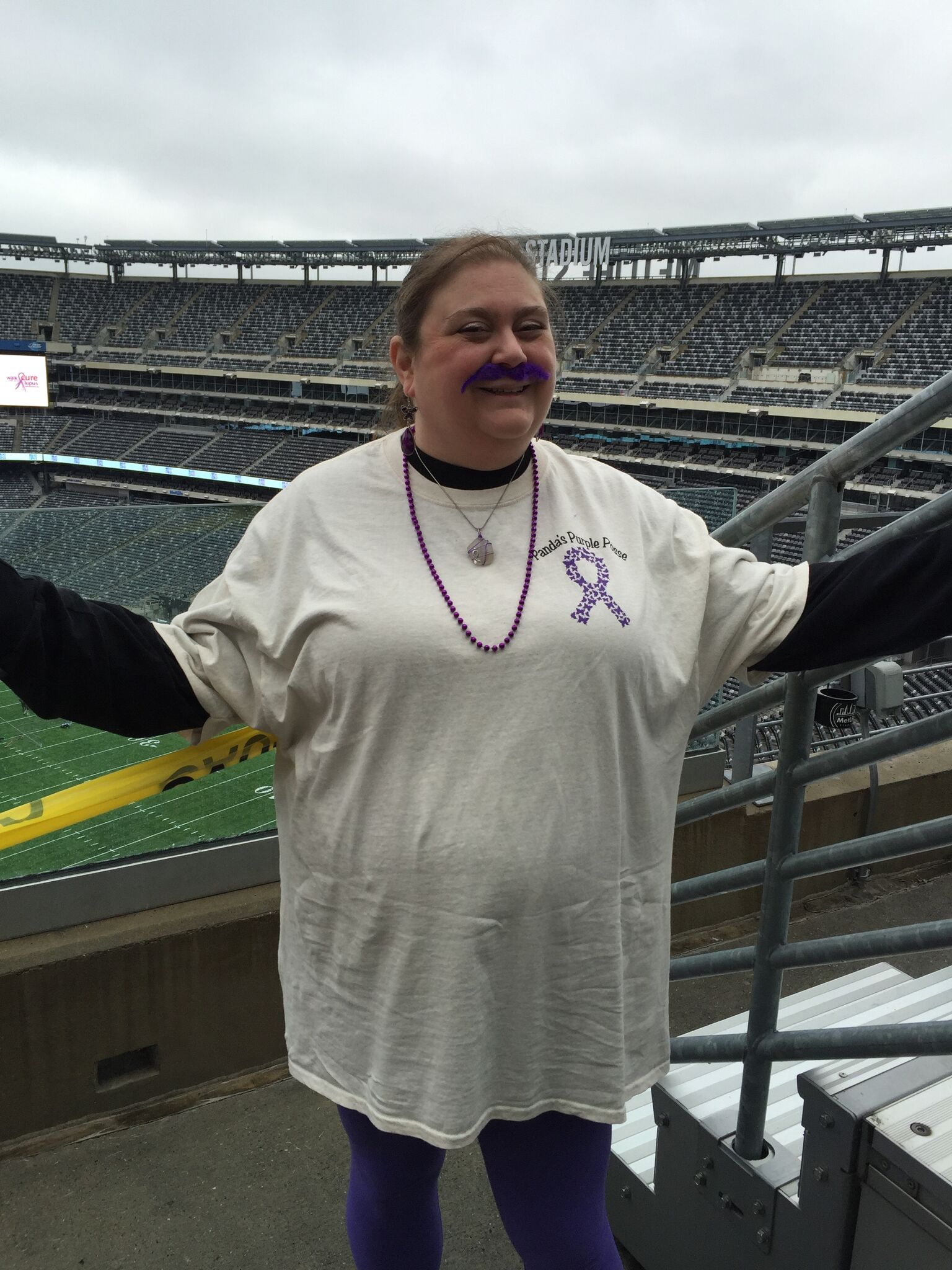 woman wearing a lupus awareness tshirt and standing in a baseball stadium
