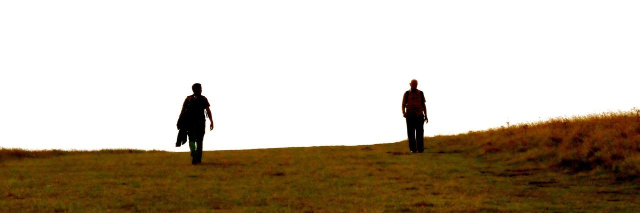 two people walk down a hill together