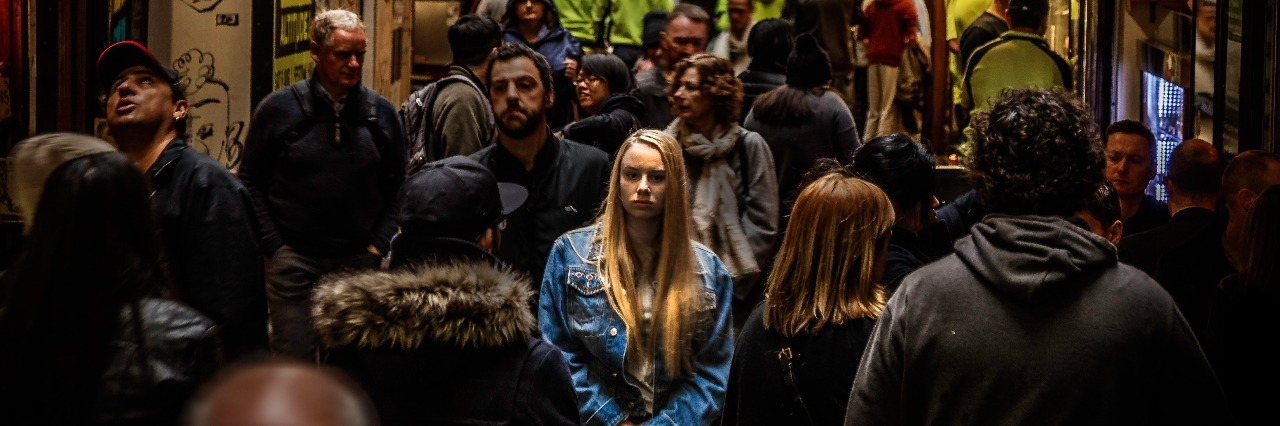 young woman looking sad while standing alone in busy street