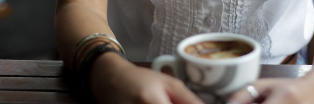 woman with arm tattoo sitting with coffee at wooden table