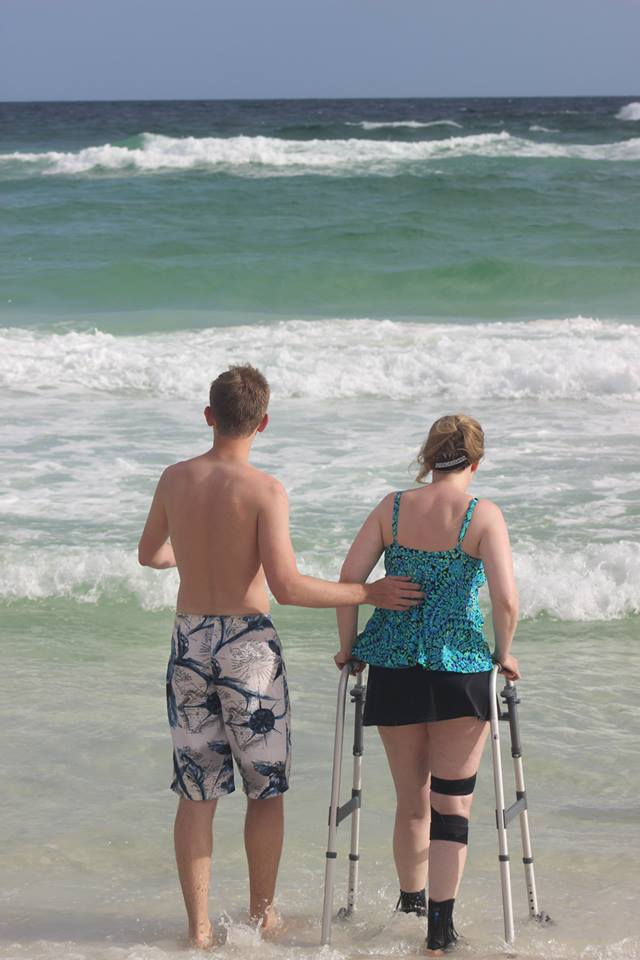 The author with her walker and her son next to her, both walking on beach toward water