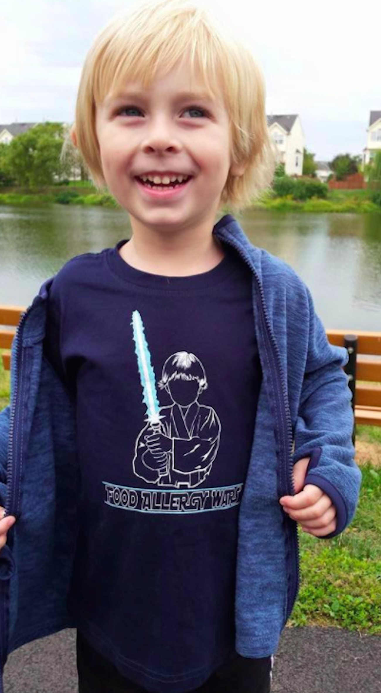 Boy wearing a jacket over a t-shirt that says food allergy wars and has an illustration of a boy holding a lightsaber